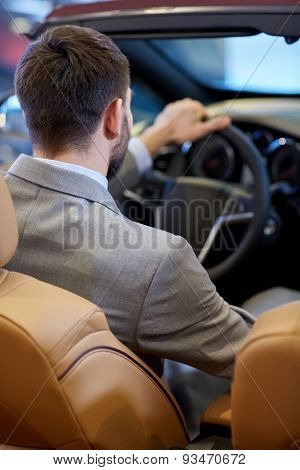 auto business, car sale, lifestyle and people concept - close up of man sitting in cabriolet car at auto show or salon