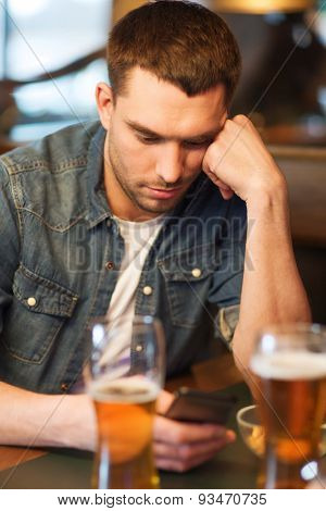 people and technology concept - man with smartphone drinking beer and reading or sending message at bar or pub
