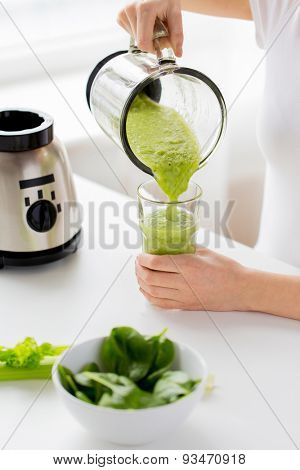 healthy eating, cooking, vegetarian food, dieting and people concept - close up of young woman with green vegetables pouring detox shake or smoothie from blender jar to glass at home