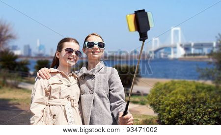 people, children, friends and technology concept - happy girls taking picture with smartphone on selfie stick over tokyo rainbow bridge in japan background