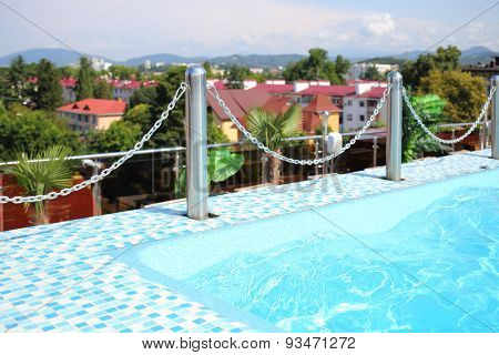Blue swimming pool on the rooftop before surrounding area