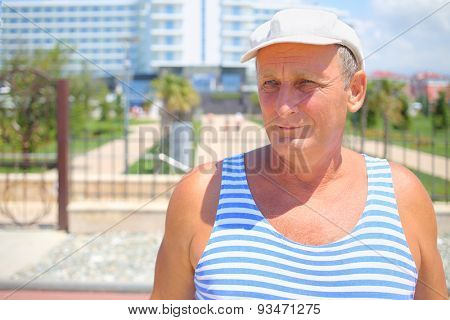 Portrait of senior in a striped vest and a white cap in front of the resort hotel