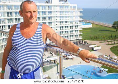 Portrait of elderly man in striped vest on the terrace