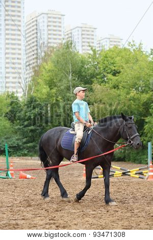 Boy in blue shirt riding a horse in park near the apartment complex