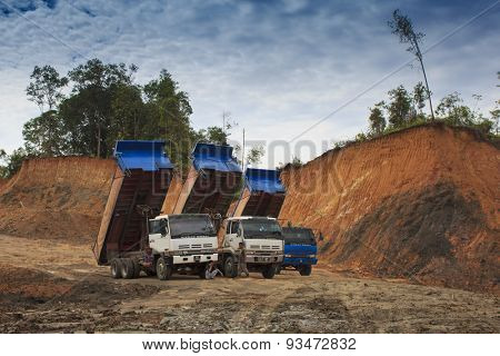 KUCHING, MALAYSIA - MAY 25 2015: Deforestation. Trucks ready to cart away timber as rain forest is destroyed in Borneo.