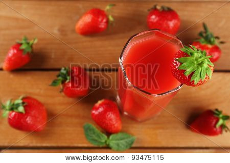 Glass of fresh strawberry juice on wooden background