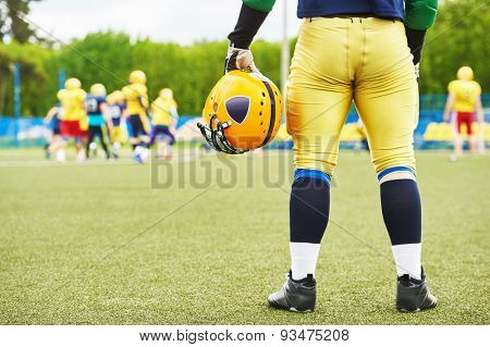 American football player with helmet in hand watching the game