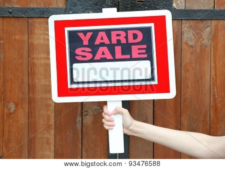 Wooden Yard Sale sign in female hand on wooden fence background