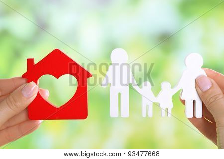 Female hands holding model of house and paper family on bright background