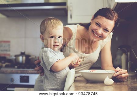 Mom with her 2 years old child cooking holiday pie in the kitchen to Mothers day, casual lifestyle photo series in real life interior