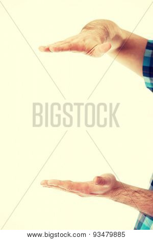Male's hands holding something invisible.
