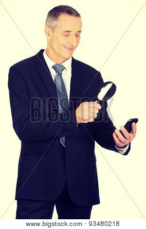 Businessman with magnifying glass and mobile phone.