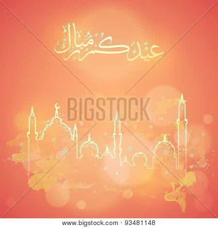 Arabic calligraphy text of Eid Mubarak with mosque on shiny orange background for muslim community festival celebration.