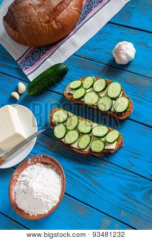 Freshly Baked Bread, Floar, Sandwich With Sliced Cucumbers And Butter On Dish In Rural Or Rustic Kit