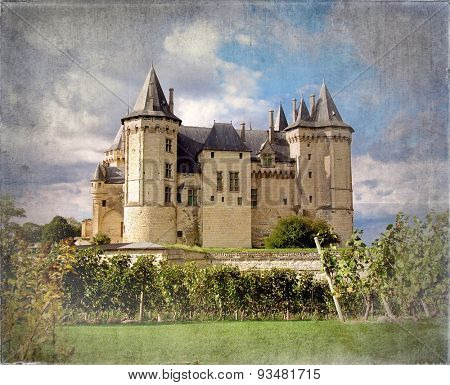 Saumur Chateau with dramatic sky behind and grapevines in the foreground. Vintage style processing