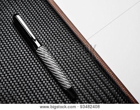 Luxurious rollerball pen on a carbon surface