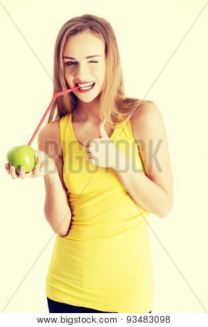 Attractive young woman in yellow top is drinking from and apple with a straw and showing OK. Isolated on white.
