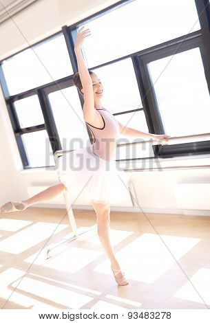 Ballerina Doing Barre Exercises In Sunny Studio
