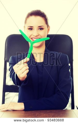 Smiling businesswoman holding small windmill