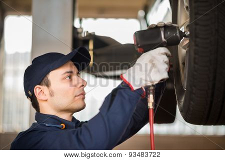 Portrait of a mechanic replacing a wheel