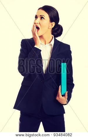 Shocked businesswoman holding a binder.