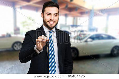 Handsome smiling car dealer lending you the keys