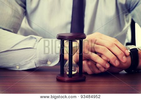 Businessman with hourglass by a desk in the office.