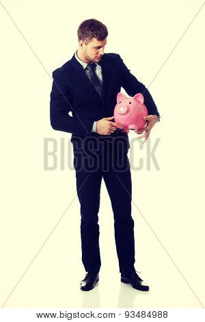 Young businessman holding a piggybank.