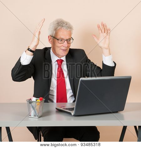 Senior man happy while working with laptop at the office