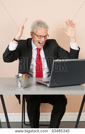 Senior man scaring while working with laptop at the office