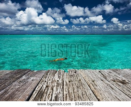 Man snorkeling in crystal clear turquoise water at tropical beach