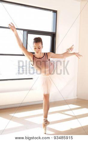 Ballerina In Arabesque Position In Dance Studio