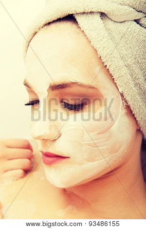 Young spa woman relaxing with cream moisturizer.
