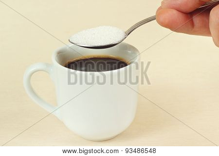 Hand pours sugar from a spoon in coffee cup