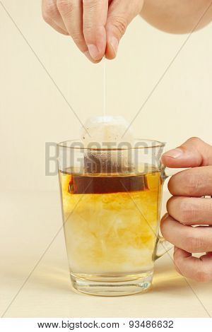 Hands brewed fresh tea in glass with hot water
