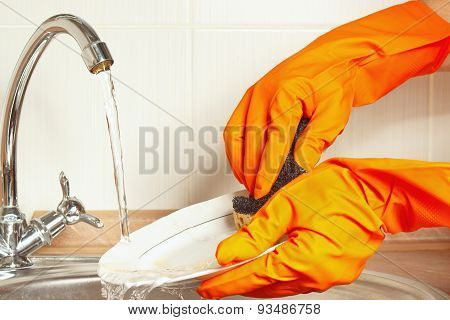 Hands in gloves wash the dirty plate under running water in kitchen