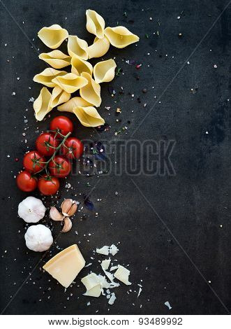 Food frame. Pasta ingredients. Cherry-tomatoes, pasta, garlic, basil, parmesan and spices on dark gr