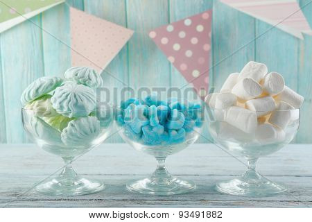 Set of candies in glassware on wooden background