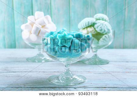 Fluffy candies in glassware on wooden background