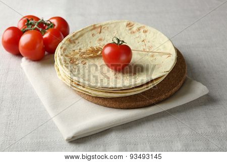 Stack of homemade whole wheat flour tortilla on napkin, on light background