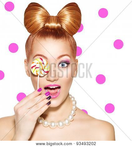 Beauty fashion model girl Eating colourful lollipop. Surprised Young funny woman with bow hairstyle, pink nail art and makeup isolated on white with pink polka dots background
