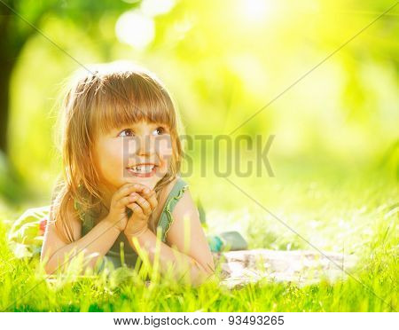 Portrait of a smiling little girl lying on green grass. Cute three years old child enjoying nature outdoors. Healthy carefree kid playing outside in summer park. Copy space for your text