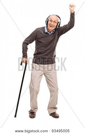 Full length portrait of an overjoyed senior holding a cane and listening to music on headphones isolated on white background