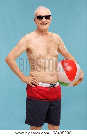 Vertical shot of a shirtless senior in swim shorts holding a beach ball and looking at the camera on blue background