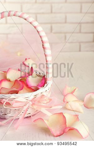 Wedding basket with roses petals and box with wedding rings on table, on light background