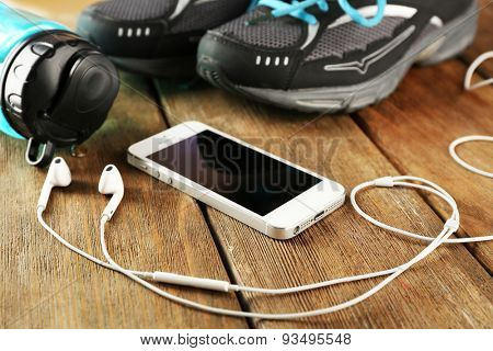 Sneakers and earphones on wooden table, closeup