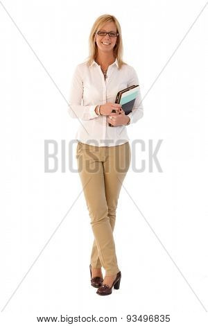 Happy blonde businesswoman holding folders, smiling, looking at camera. Full size.