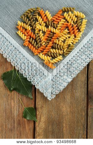 Row pasta arranged in heart shape on fabric background
