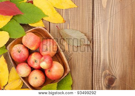 Apples in bowl and colorful autumn leaves on woden background with copy space