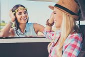 stock photo of recreational vehicles  - Two happy young women smiling and looking at each other while leaning at the vehicle door - JPG